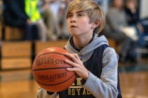Lower School boy preparing to take a shot during an Oak Knoll basketball game