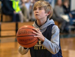 Lower School boy preparing to take a shot during an Oak Knoll basketball game