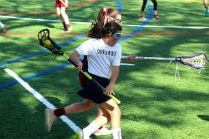 Female Lower School lacrosse player during a game at Oak Knoll