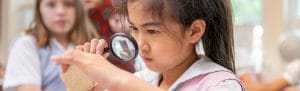 Lower School student in science glass looking through magnifying glass