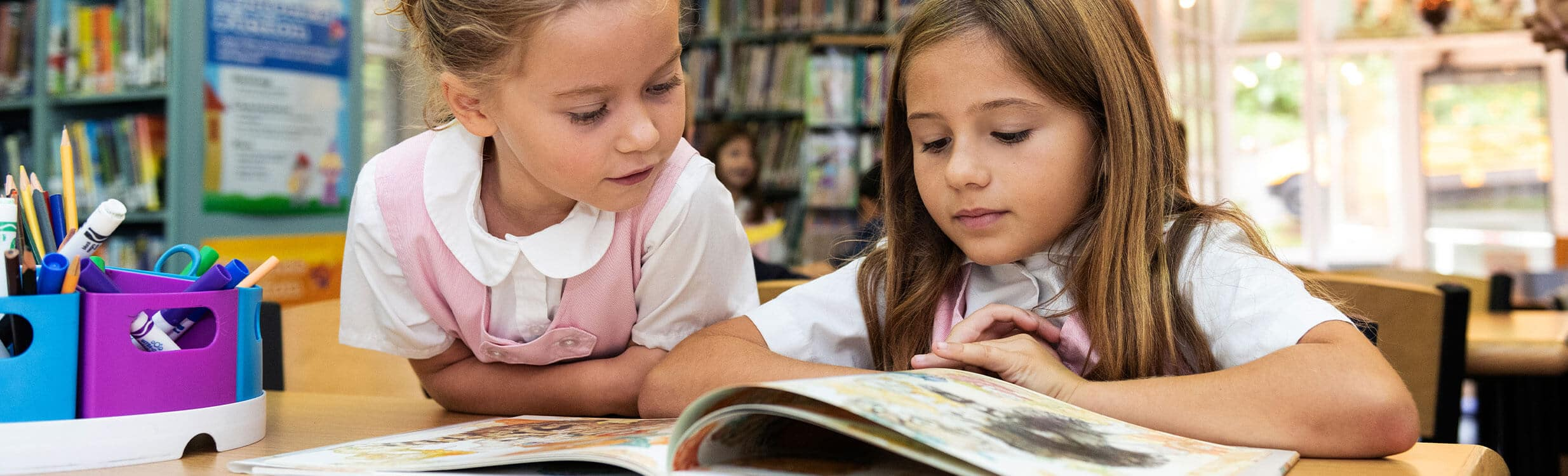 Lower School students reading together in the library.