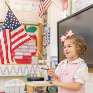 Lower School student holding American flag.
