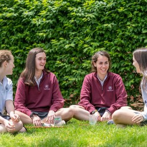 Upper School girls eating lunch on the lawn.