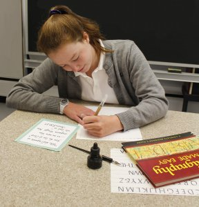 An Oak Knoll student practices calligraphy during Scribes club