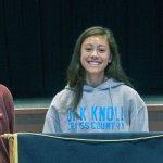 Three students standing next to school podium.