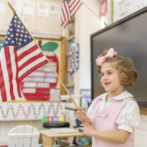 Lower School student holds the American flag.