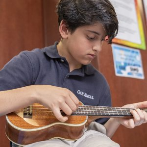 Lower School male student plays an instrument during music class.