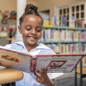 Lower School student smiles as she reads book in the library.