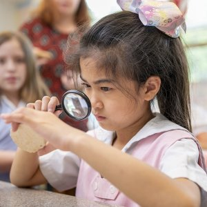 Lower School student looks through magnifying glass during science class.