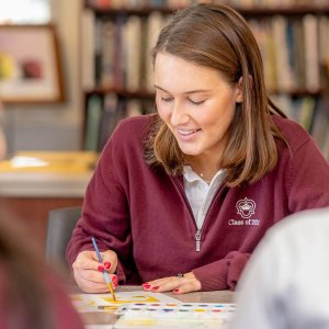 Upper School student at Oak Knoll paints during class