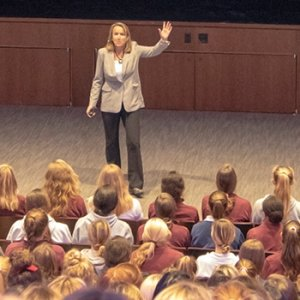 Sharon Wood addresses student audience in auditorium.