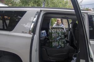 Student loading bottled water into passenger seat of a car