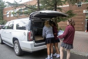 Students loading bottled water into back of a sports utility vehicle.