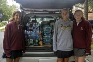 Students posing in front of donated bottled water.
