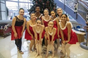 Ballet dancers pose in front of Christmas tree