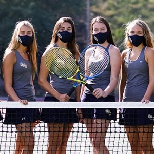 Photo of varsity tennis team and coaches next to tennis net