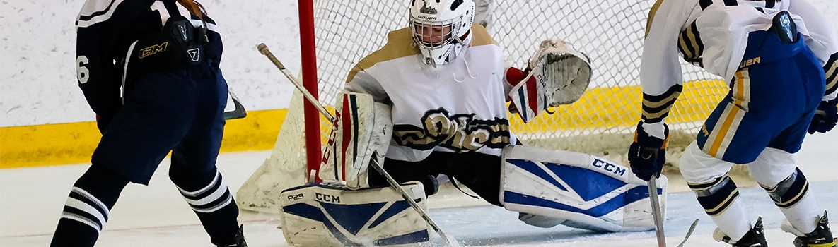 Photo of Oak Knoll ice hockey goalie making a save on an opponents shot attempt.
